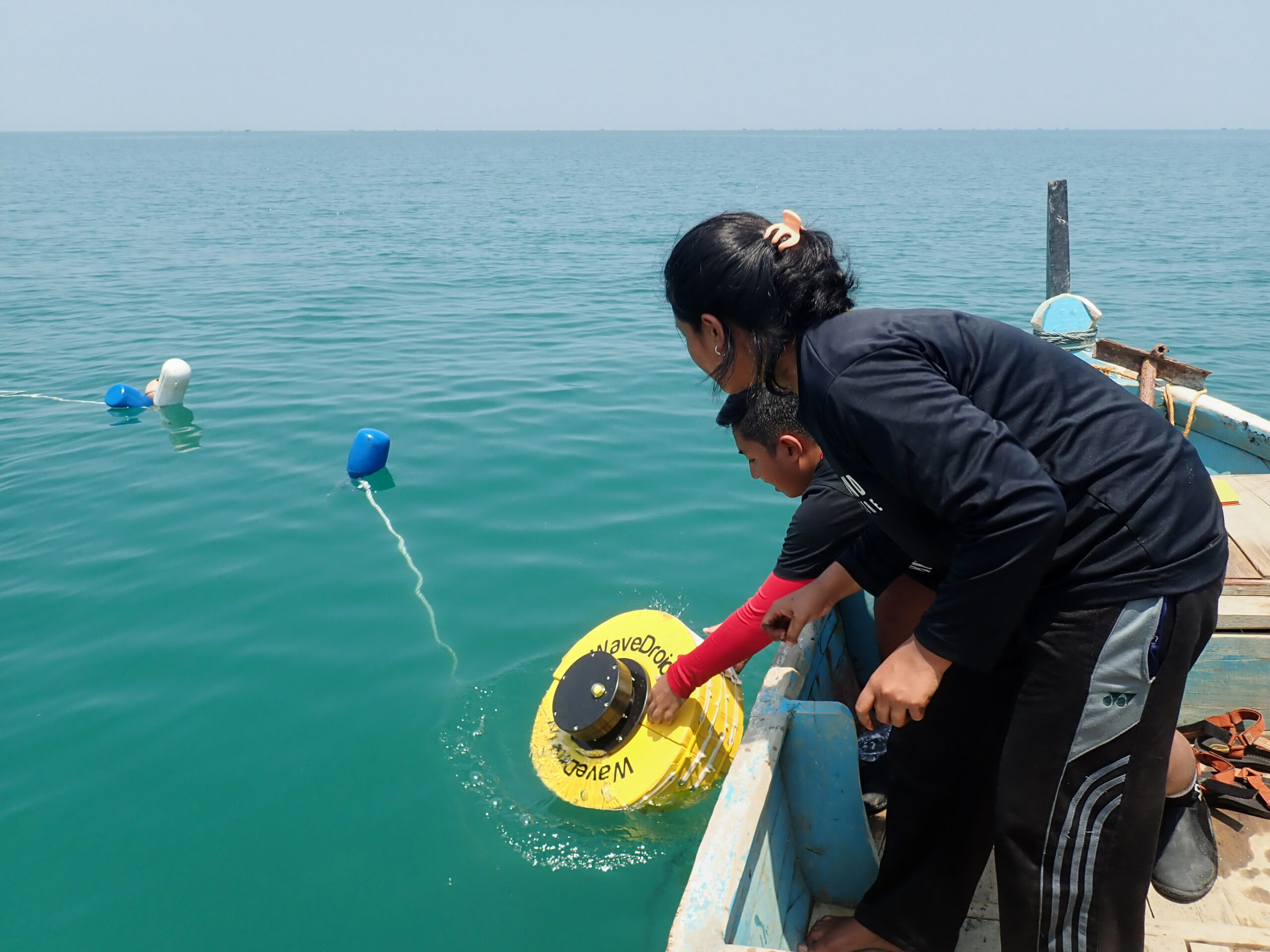 Two students deploying the WaveDroid in the Java Sea. (c) Silke Tas
